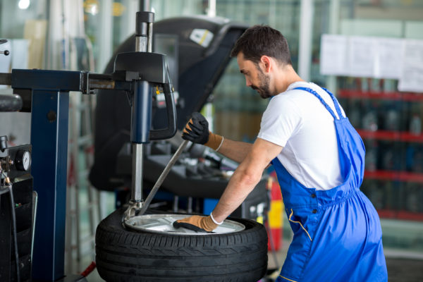 mechanic replace tires on wheels in a workshop